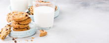 Stack Of Chocolate Chip Cookies On Blue Stone Plate With Glass Of Milk On Light Gray Background. Selective Focus. Copy Space. Banner.
