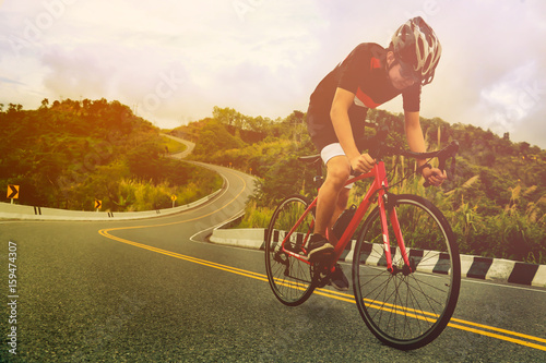 Tablou Canvas Asian man is cycling road bike in the morning