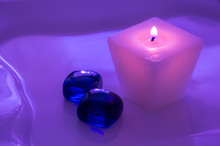 A Pink Burning Candle With Glass Blue Pebbles. Candle For Spa Salons. Purple Toning..