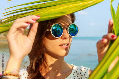 Poster Magasin de musique Close up portrait of a beautiful slim woman in fashion round sunglasses and white shirt push through palm leaves to the sun. Beauty sunshine cute girl on a sand beach with large stone.