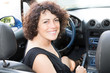 lovely cheerful woman with curly hairs in car