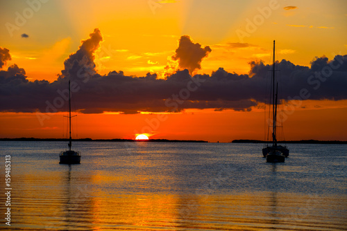 Poster Oranje eclat sunset over bay with anchored boats