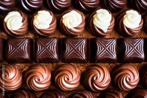 Plakat Asortowany biel, mleko i ciemny czekoladowy cukierki tło, selekcyjna ostrość
