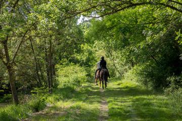 deux personnes de dos font de l'équitation sur un chemin verdoyant en pleine campagne le long d'une rivière