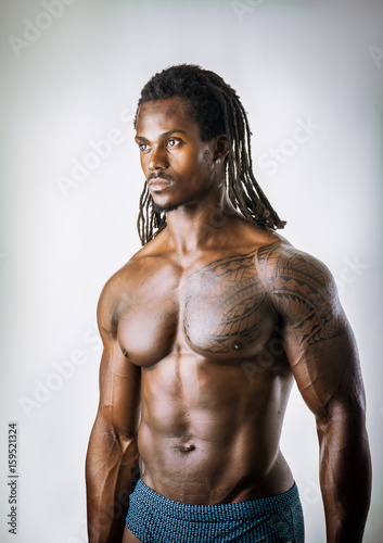 Deurstickers Akt African American bodybuilder man, naked muscular torso, wearing pants only, against white background in studio shot