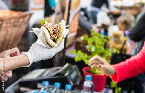 Chef handing a tortilla to a foodie at a street food market Fototapet