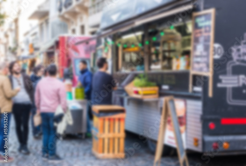 Fotografija People at a street food market festival on a sunny day, blurred on purpose