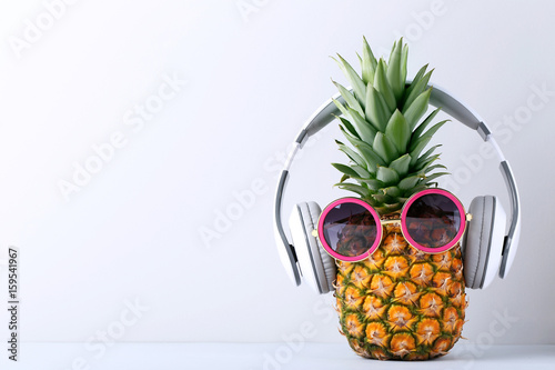 Photo sur Toile Magasin de musique Ripe pineapple with headphones on grey background