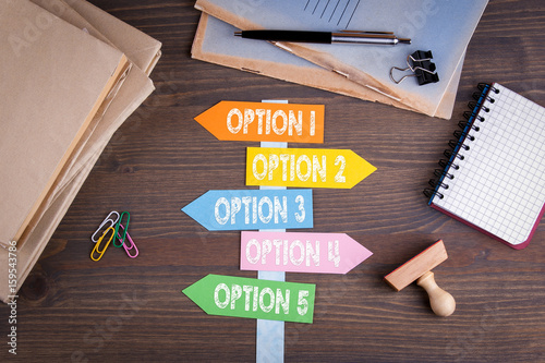 Fotografie, Obraz  option concept. Paper signpost on a wooden desk.