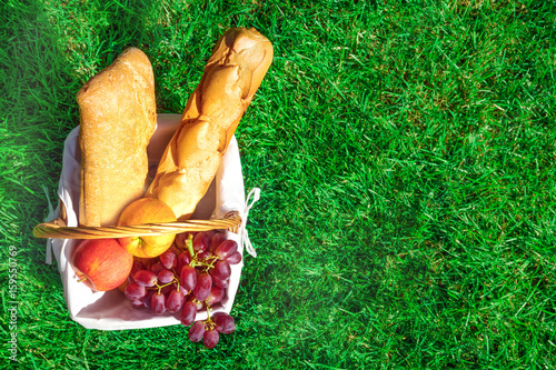 Ingelijste posters Picknick Picnic hamper with bread and fruit on green lawn