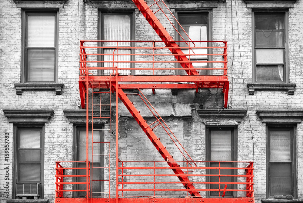 Fototapeta Red fire escape at black and white filtered residential building, New York City, USA.