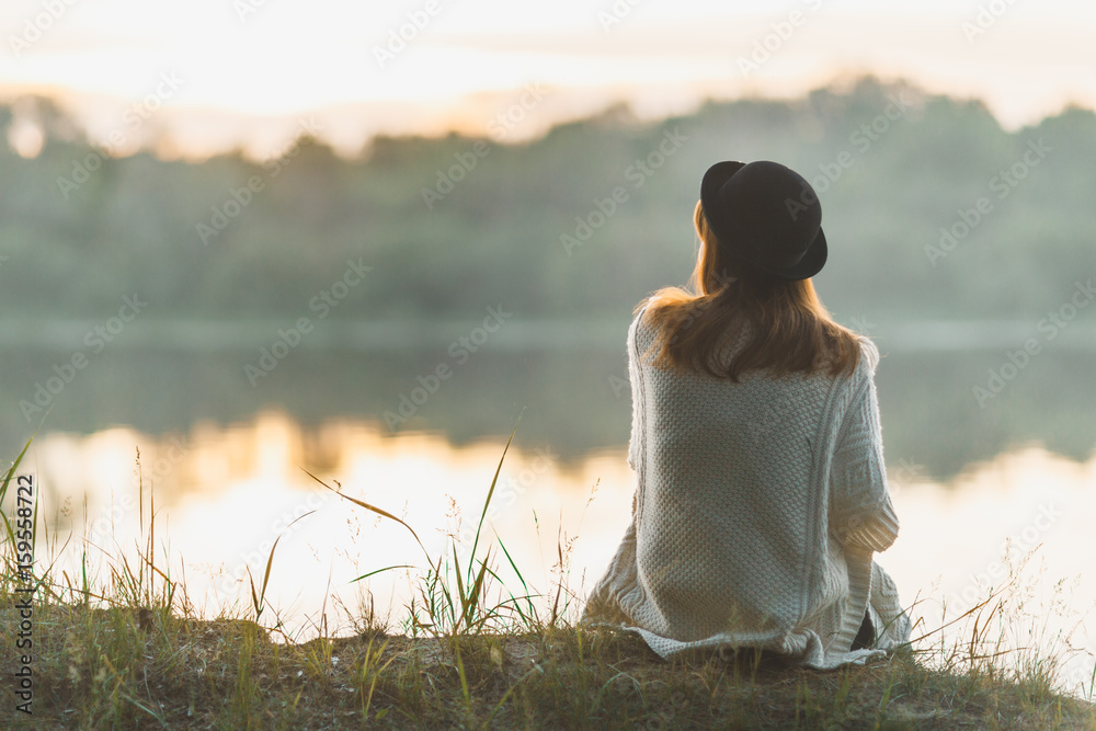 Fototapety, obrazy: A girl sitting on the river bank in silence