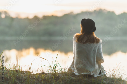 Photo  A girl sitting on the river bank in silence
