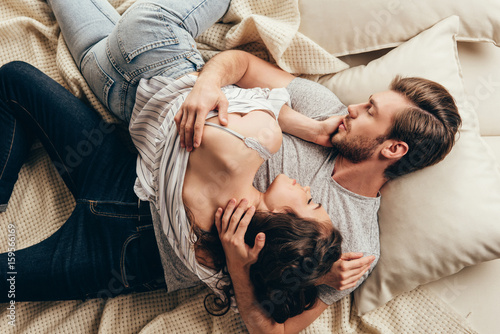 High Angle View Of Beautiful Young Couple In Love Hugging While Lying On Bed