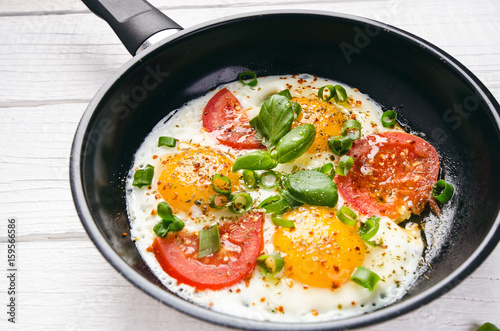 Foto op Plexiglas Gebakken Eieren Pan of fried eggs with tomatoes, cheese, spring onion, herbs on a white table. White wooden table. Concept of food. Breakfast time. Copy space.