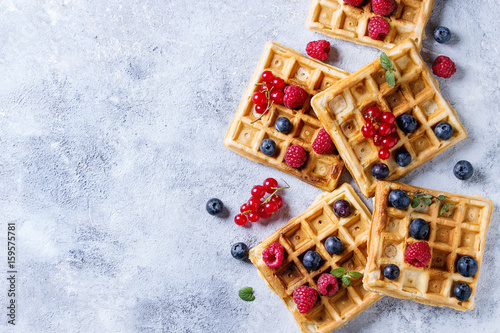 Fotografía  Homemade square belgian waffles with fresh ripe berries blueberry, raspberry, red currant over gray texture background