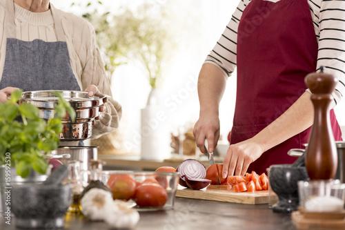 Foto op Plexiglas Koken Woman cutting tomatoes