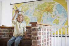 Boy Sitting In Front Of World Map Playing With Toy Aeroplane
