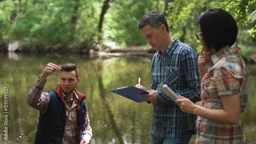 Fotografie, Tablou Three ecologists wearing casual clothing exploring lake and taking water sample