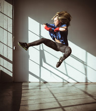 Full Length View Of Young Woman In Gym In Mid Air In Kickboxing Stance