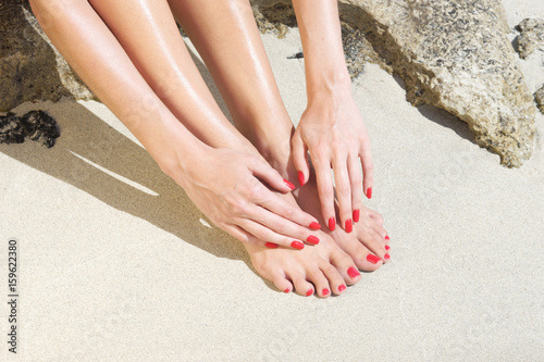 Poster Pedicure Pretty woman feet with red manicure and pedicure: relaxing on sand. Holiday, vacation, spa, summer: concept.