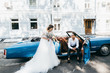 canvas print picture - Just married couple in the blue retro car on their wedding