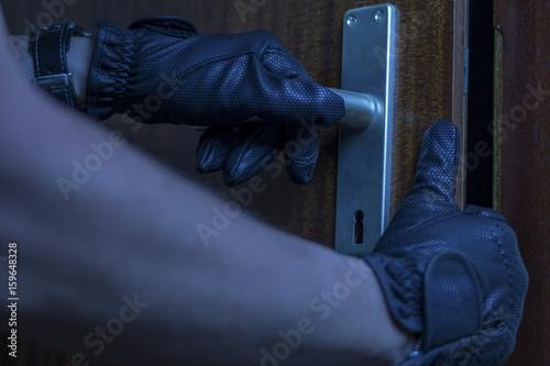 Fényképezés  Ein Einbrecher öffnet eine Tür