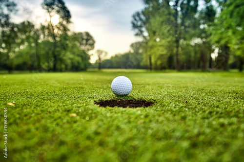 Golf ball on the green. golf ball on lip of cup Fotobehang
