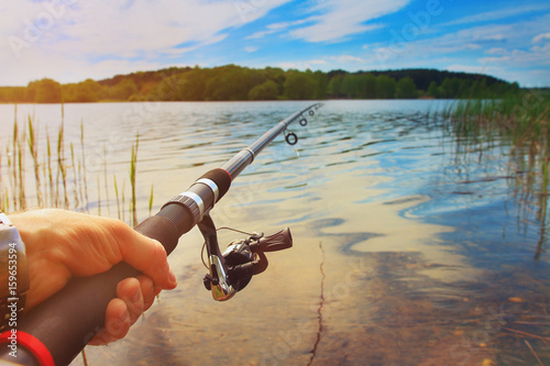 Printed kitchen splashbacks Fishing fisherman is fishing on a forest lake outdoors on a bright summer day