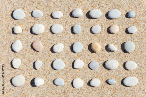 Plakat  Pattern of white stones on sand background. Flat lay, top view