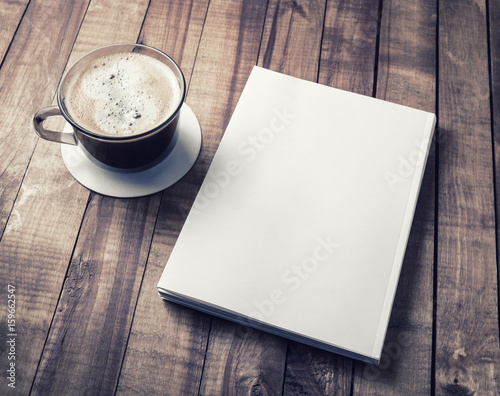 Fototapeta Blank closed book and coffee cup on vintage wooden background. Responsive design template. obraz