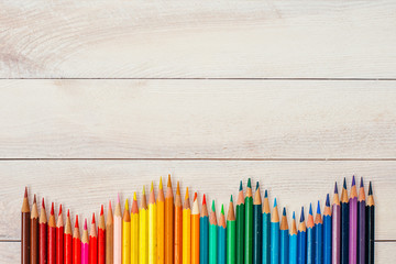 Fototapeta Do przedszkola Colored pencils on white wooden background, top view. Copy space.