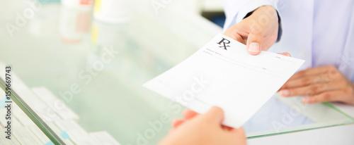 Valokuva  Customer (patient) giving prescription to pharmacist in drugstore
