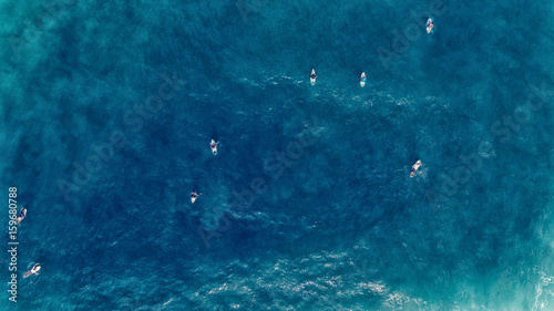 Aerial view of Surfer swimming on board near huge blue ocean wave