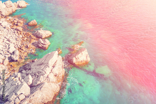 Fotobehang Lichtroze Rocky seashore, top view in the sunlight