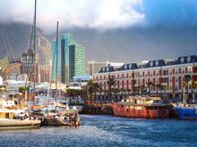 Victoria And Alfred Waterfront Has Sweeping Views Of The Atlantic Ocean, Table Bay Harbor, Behind Clouds Floating On Table Mountain With Dark Blue Sea And Blue Sky Background, Cape Town, South Africa