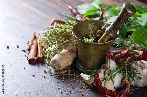 Different herbs and spices on a wooden table . Wallpaper Mural