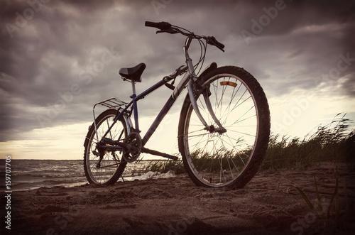 Fotobehang Fiets Bicycle near lake during sunset.