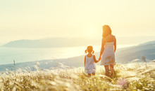 Happy Family In Summer Outdoors. Mother And Child Daughter Stand With Their Backs On Sunset