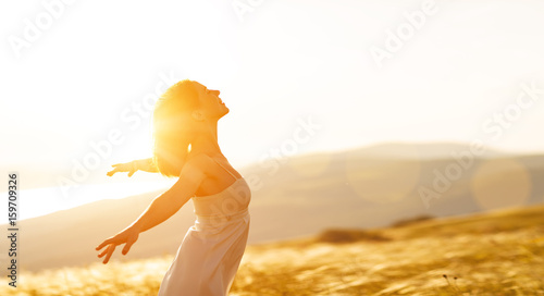 Stampa su Tela Happy woman standing with her back on sunset in nature iwith open hands