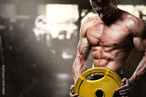 Fotografia  Middle aged bodybuilder posing in gym with weight
