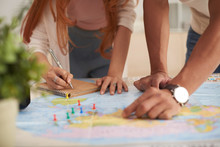 Closeup Shot Of Young Couple  Marking Travelling Destinations On Map And Planning Vacation Budget
