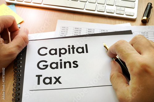 Foto  Hands holding documents with title capital gains tax CGT.