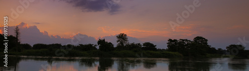 Aluminium Prints Dark grey panorama sunset in sky beautiful colorful landscape silhouette tree woodland and river reflect the twilight time
