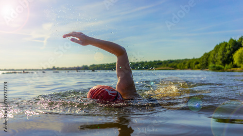 Fotomural  Woman swimming in a lake