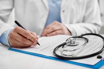 Woman practitioner in uniform prescribing recipe for medical treatment. Healthcare concept.