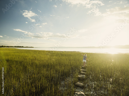 Small girl (4-5) walking on stepping stones in meadow - 159767360