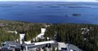 Koli hotel, Cinema 4k tilt aerial view of pielinen lake and tilting down to koli mountain and the hotel on top, on a spring day, in Lieksa, Karelia, Finland