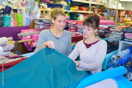 Fényképezés  middle-aged dressmaker looking for fabrics at store