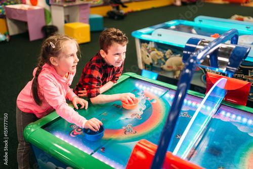 Fotomural Little kids plays air hockey, entertainment center